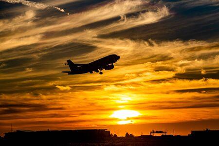 Urlaubsflug in einen farbenfrohen orangefarbenen Sonnenuntergang
