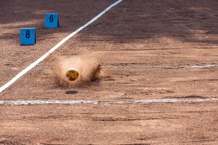 sphere landing in the sand at the shot put competition in stadium
