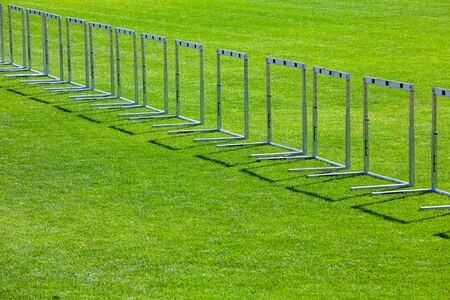 many hurdles standing on grass as a border