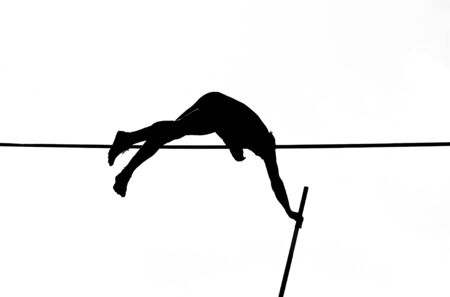 pole vault springer crossing the bar in black and white