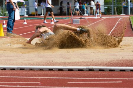landing in the sand at the long jump during competition