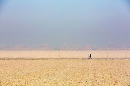one person walks alone on a field along a long fence