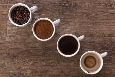 Four cups of coffee, phases of drink - bean, ground and empty cup