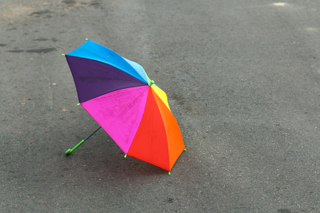 friendless: Rainbow umbrella lying on the pavement after the summer rain, forgotten by a child. Sadness and loneliness
