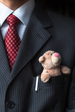 breast pocket: The elegant stylish businessman keeping cute teddy bear in a his breast suit pocket. Formal negotiations concept