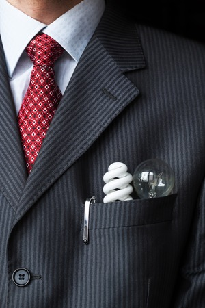 The elegant stylish businessman keeping two different light bulbs - Incandescent and fluorescent energy efficiency - in his breast suit pocket. Energy saving concept. Environment protection theme Stock Photo