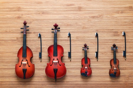 cellos: Set of four toy string musical orchestra instruments: violin, cello, contrabass, viola on a wooden background. String Quartet. Music concept. Cello and three violins, all vintage instruments. Stock Photo