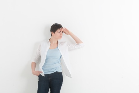 Young woman in white shirt holding his hand over her eyes. Be careful. Beautiful girl on a white background. Space for text.