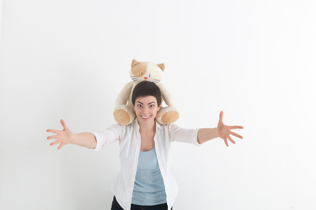 Success positive emotions. Happy young woman in white shirt stretching hands ahead, wanting to hug someone. Plush cat sits on her neck.