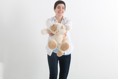 Young pretty woman with short hair in casual style giving forward plush toy cat and looking at camera with tooth smile face. Studio shot on a light grey background