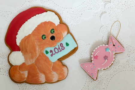 Two gingerbread cookies in the shape of Christmas dog and candy on a white napkin background. Top view, flat lay, copy space. Curly Christmas gingerbread home cooking. Happy new year 2018.