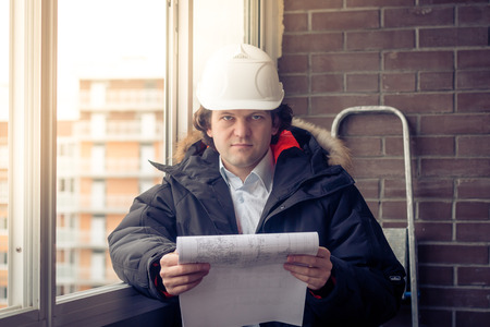 Portrait of an architect builder studying layout plans of building. Soft focus, toned