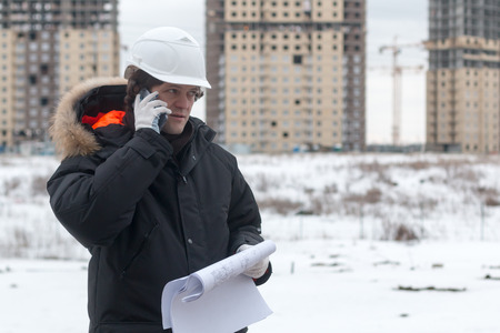 Architect, engineer, project manager or Senior engineer man talking on CB phone to building in the city with a blank plan as for construction. Soft focus Reklamní fotografie