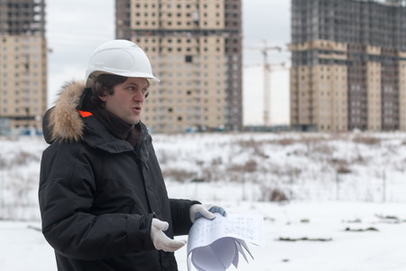 Worker or engineer holding drawing in hands and reading it on background of new apartment buildings and construction cranes on background. Architect engineer concept. Soft focus. 写真素材