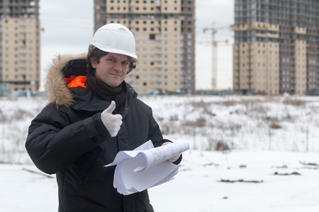 Worker or engineer holding drawing in hands and reading it on background of new apartment buildings and construction cranes on background. Architect engineer concept. Soft focus