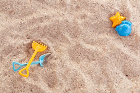 Bright plastic childrens toys in the sand. Concept of beach recreation for children. Childrens summer games. Summer concept. Flat lay, top view, copy space, blue and yellow. 스톡 콘텐츠