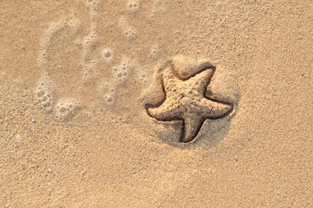 Starfish drawn on the beach sand being washed away by a wave. Foaming sea wave coming to wash a picture on wet yellow beach sand. Holiday and vocation message. View from above. Copy space. Stock fotó