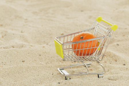 Shopping cart with tangerine mandarin fruit standing on the sand. New year fruit. Healthy diet food.
