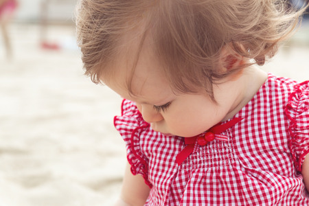 Close up nine month old baby girl on the beach background. Little pretty cute european infant child with dark hair in red plaid shirt sitting on the sand of the beach and looking down. Selective focus Reklamní fotografie