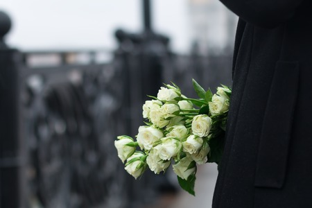 Bunch of white tea roses in the pocket of black female coat on the city background of cast iron fence. Close up Stock fotó