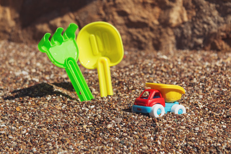 Children's toy truck with gravel or sand. Yellow scoop and green rake on the background. Concept of transportation of goods and building materials. Industrail symbols. Summer holiday by the sea