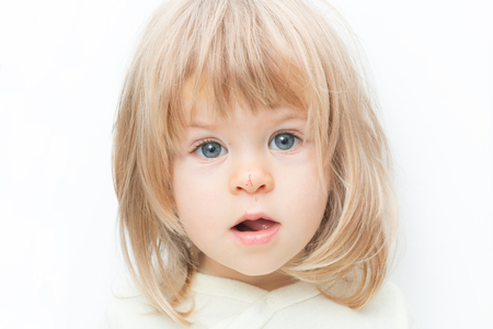 Close up portrait blond hair baby girl with a scratch on her nose isolated on the white background. Surprised female toddler, keeps mouth opened. Child safety concept, injuries from falling down