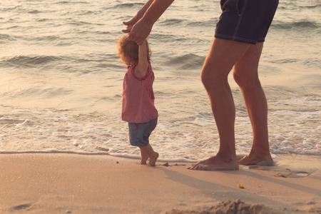 Father helping his baby with the first steps, teaching baby to walk concept, outdoor candid photo on the beach, spending a day at the beach, healthy family lifestyle.