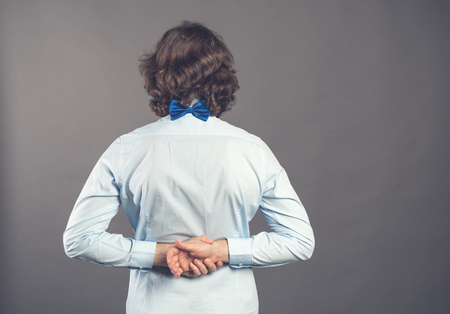 Back view of man in blue shirt and bow tie. Standing young guy. Rear view people collection. Backside view of person. Isolated over grey background. A male stands with his hands folded back in lock. Reklamní fotografie