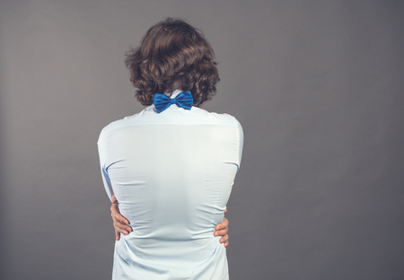 Young man in blue shirt and bow tie hugs himself on grey background. Rear view. His hands lie on waist. He needs to be embraced. Selfish feeling, love yourself concept. Positive emotion. Copy space