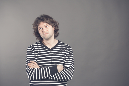 Portrait of caucasian man with bored fed up expression, looks displeased up, being tired to explain his wife where he was at night. Shaggy guy in stripes shirt tired and bored to listen to bullshit.