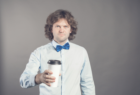 Close up portrait of happy handsome man in blue shirt with paper cup of morning coffee. Good morning with tea. Takeaway coffee, time for coffee break. Waiter offers coffee-to-go. Toned. Copy space