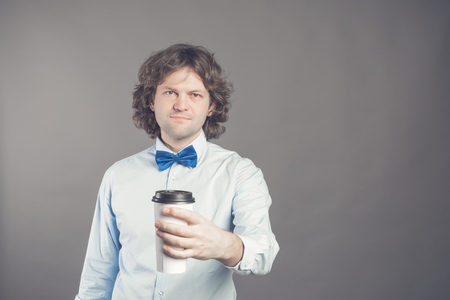 Portrait of happy handsome man in blue shirt and bow tie with paper cup of morning coffee. Good morning with tea. Take away coffee, time for coffee break. Waiter offers coffee to go. Toned Copy space Reklamní fotografie