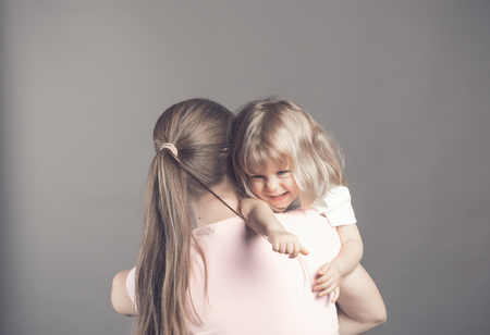 Laughing little girl looks happy in mothers arms. Beautiful baby girl pulls moms hair and smiling. Woman holding her daughter staying on the grey background. Rear veiw. Happy family and love concept Reklamní fotografie