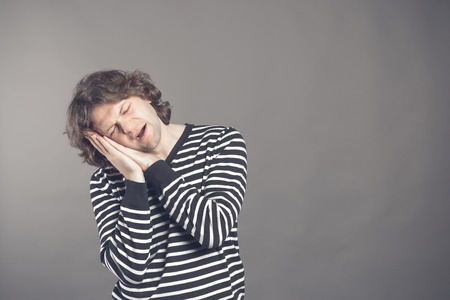 Young man in striped black and white sweater wants to sleep. Put his head in his hands and closed eyes while yawning. Standing on the grey background. Hands under his cheek. Insomnia concept.