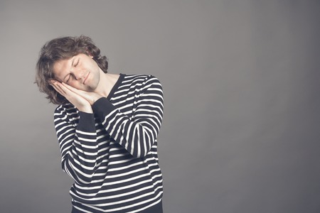 Young man in striped black and white sweater wants to sleep. Put his head in his hands and closed eyes while smiling. Standing on the grey background. Hands under his cheek. Insomnia concept.