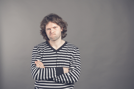 Closeup portrait of displeased, angry, grumpy man in striped sweater bad attitude, arms crossed, folded, looking at you, isolated gray background. Negative human emotion, facial expression, feeling. Reklamní fotografie