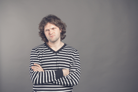 Portrait of displeased male model looks angrily with sullen expression, keeps arms crossed, wears striped sweater, isolated over studio wall. Frustrated serious gloomy caucasian man stands indoor. Reklamní fotografie