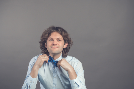 Studio shot of young male hipster adjusting his bow-tie in mirror isolated on grey background. Dark curly hair groom in blue shirt preparing for meeting with the bride. Looking at camera and smiling.