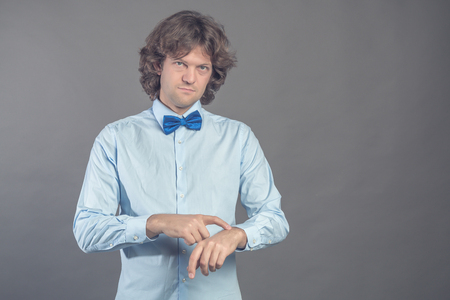 Punctual serious man points at wrist, being worry as lates for meeting wears blue shirt and bow tie stares straiht at camera and lightly smiles. Guy checks time over grey background. Time out concept.