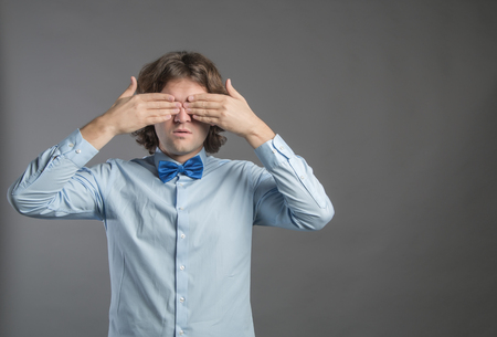 Man covering his eyes with hands on gray background. Shy male closing eyes by hands cant see hiding, wall background. See no evil concept. Negative human emotion, facial expression, feeling reaction.