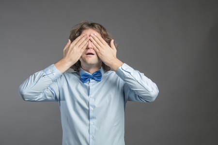 Shocking news. Portrait of young man in blue shirt and tie covering eyes with hands and open mouth while standing against grey wall background. Negative emotion, facial expression, feeling reaction.