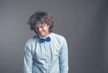 Portrait of unhappy hophead man standing and looking aside with melancholy. Isolated on grey background wearing blue shirt and bow tie. Hunched shoulders lowered Poorly sleeping or insomnia concept.