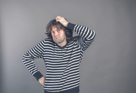 Puzzled guy with messy hair, frowning and looking unsatisfied scratching head, thinking deeply about something on grey wall background. Human facial expression, emotion, feeling, sign body language.