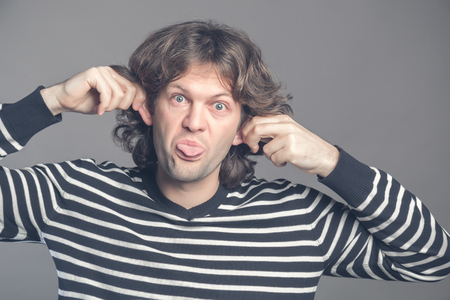 Close up of man making silly monkey face isolated on grey background. Guy grimaces monkey. Funny male holding his ears and shows tongue looks like monkey, pretending chimpanzee, entertaining children