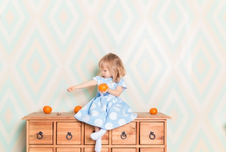 Portrait of blonde Caucasian baby girl with blue eyes in elegant dress and white socks sitting on wooden dresser with tangerine clementine fruit in hand and looking sideways at her hand. Amazement 스톡 콘텐츠