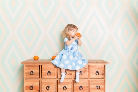 Portrait of little girl in blue polka dot dress and white socks with tangerine in hands sitting on wooden commode and going to eat it. Wallpaper on the background. Vitamins, fruit and childrens joy