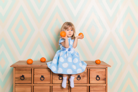 Toddler child baby girl in light blue dress seriously sitting on the wooden chest of drawers and holding fresh orange mandarins in her hands on rhomb wallpaper background. Winter holidays or christmas Reklamní fotografie