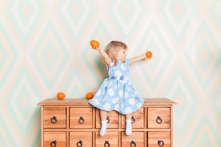 Little girl holding tangerines or oranges in her hands while sitting on the wooden wardrobe. Wearing light blue dress. Christmas holidays is over. Happy smiling baby raising hands up looking aside