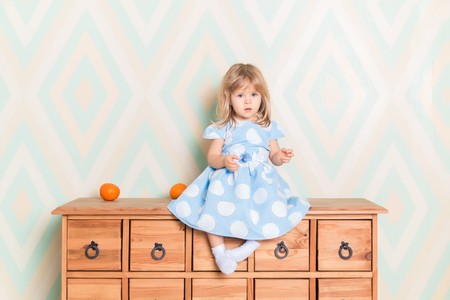 A little baby girl in her room sitting cross-legged on chest of drawers with tangerines on the rhomb wallpaper background. Child in blue polka dot dress and white socks attentively looking at camera.