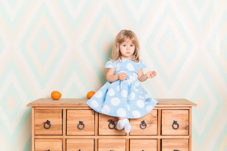 A little baby girl in her room sitting cross-legged on chest of drawers with tangerines on the rhomb wallpaper background. Child in blue polka dot dress and white socks attentively looking at camera